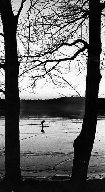 Concord, MA - 2/13/1981: A man fishes in Walden Pond in Concord, Mass. at sunset on Feb. 13, 1981. (Stan Grossfeld/Globe Staff) --- BGPA Reference: 140411_MJ_010