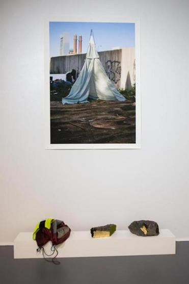 "Kate Gilbert installs her photo ""Untitled (Chinatown Housing)"" above rocks and asphalt adorned with gold leaf, moss, and a nylon sack."