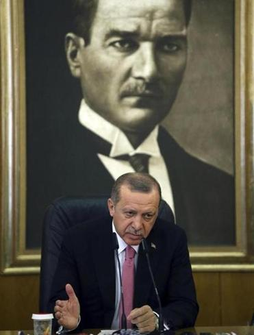 Backdropped by a picture of Mustafa Kemal Ataturk, the founder of modern Turkey, Turkey's President Recep Tayyip Erdogan talks to members of the media in Istanbul.