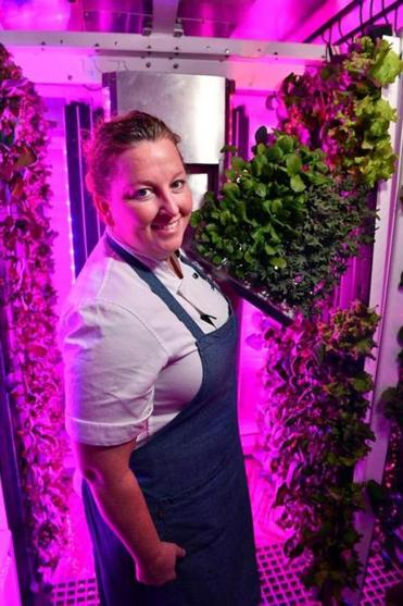 Chef-owner Mary Dumont with broccoli rabe and mizuna grown in the on-site hydroponic garden inside a modified shipping container.