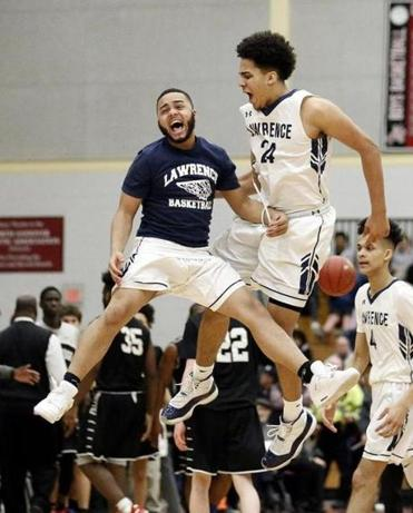 Lawrence's Luis Reynoso, right, celebrates with a teammate during the second half of their win over Cambridge in their D1 North semifinal game in North Andover, Mass., Tuesday, March 6, 2018. (Winslow Townson for The Boston Globe)