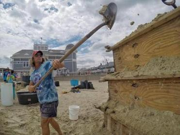 A competitor shoveled sand from his 10-ton allotment on Hampton Beach on Wednesday, ahead of the start of the 18th annual competition.