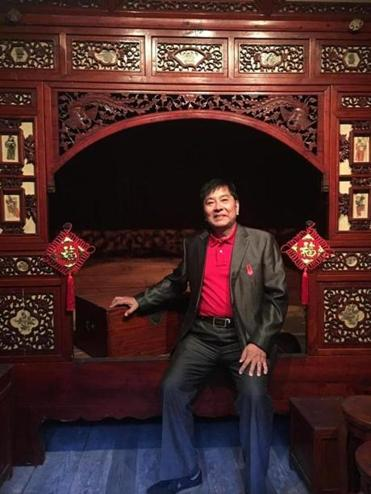 Huang Binggen sitting on his parents' marriage bed in the Yin Yu Tang house in 2016.