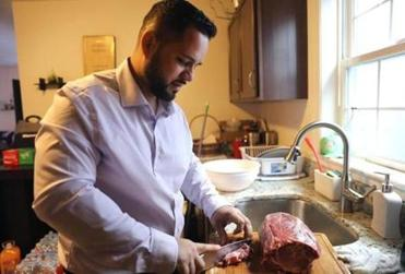 """Revere, MA - 12/30/18 Washington Santos (cq) pitches in to prepare a meal with his wife Priscila Santos (cq), and 13-year-old daughter Rebecca Santos (cq), during the Patriots game. His 14-year-old son Matthew Santos (cq) watched. According to a judge, Santos was erroneously denied """"welcome home"""" pay after he was discharged from the U.S. Army. Photo by Pat Greenhouse/Globe Staff Topic: 31veterans"""