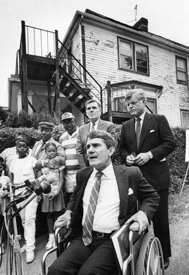 Boston, MA - 6/22/1987: New England regional administrator of the Environmental Protection Agency Michael R. Deland speaks during the announcement of an E.P.A. soil cleanup program outside the home of the Jones family in the Dorchester neighborhood of Boston on June 22, 1987. Joining Deland are U.S. Senator Ted Kennedy, standing right, Boston Mayor Ray Flynn, standing center, and members of the Jones family, standing left. (George Rizer/Globe Staff) --- BGPA Reference: 190109_BS_023