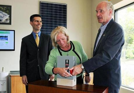 Jeff Morrill (left) watches as state Representative Rhonda Nyman and US Representative Bill Keating flip the switch.