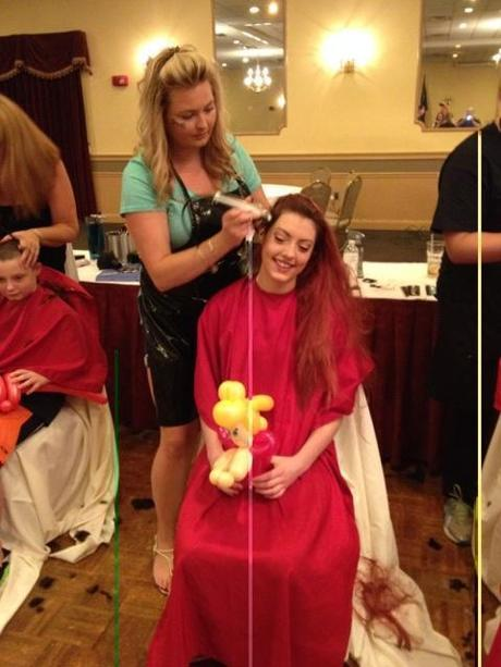 Jamie Lee Higgins gets her head shaved Monday morning.