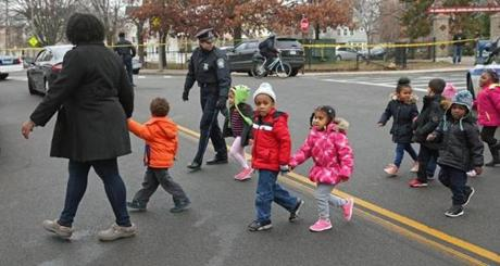 Officer Rachel McGuire (center) helped escort children from ABCD's Head Start preschool Friday. The students went to a nearby Walgreens after the shooting near them.