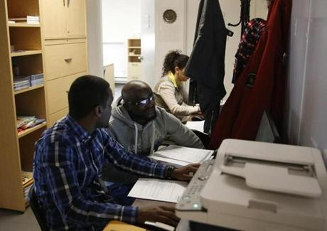 Winnipeg, Manitoba -- 3/23/2017 - A refugee from Cameroon (C) gets help from a staff member to file the proper forms needed to seek asylum in Canada at the Welcome Place. (Jessica Rinaldi/Globe Staff) Topic: Reporter: