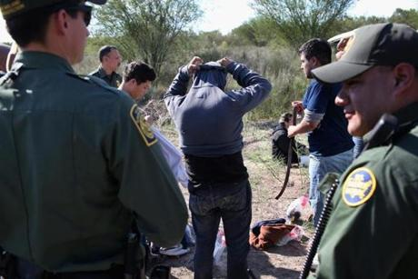 RIO GRANDE CITY, TX - DECEMBER 07: Undocumented immigrants remove items of clothing while being searched by U.S. Border Patrol agents who caught them on December 7, 2015 near Rio Grande City, Texas. Border Patrol agents continue to detain hundreds of thousands of undocumented immigrants trying to avoid capture after illegally crossing into the United States, even as migrant families and unaccompanied minors from Central America cross and turn themselves in to seek assylum. (Photo by John Moore/Getty Images)