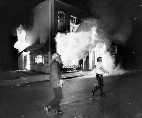 Boston, MA - 6/3/1967: A fireman and police man run up Lenox Street near Tremont Street while a laundry mat burns after being set on fire during riots in the Roxbury neighborhood in Boston on June 3, 1967. (Tom Landers/Globe Staff) --- BGPA Reference: 140909_MJ_004