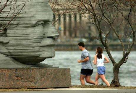 Boston-3/23/2007- Two joggers pass by the memorial statue of Arthur Fiedler as they run along the Charles River near the Hatch Shell of the Esplanade, where the famous conductor of the Boston Pops once conducted. Boston Globe staff photo by John Tlumacki -- Library Tag 03242007 Metro