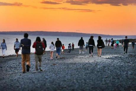 At sunset, people walk across the sand bar at low tide to Bar Island, which joins the waterfront of Bar Harbor.