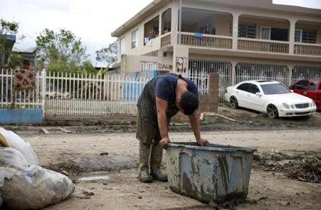 Toa Baja, Puerto Rico -- 9/30/2017 - Eric La Luz, 15, pulls a tupperware bin full of mud and detritus out of his home and onto a growing pile on Avenida Calle Palma Villa Calma after Hurricane Maria. (Jessica Rinaldi/Globe Staff) Topic: Reporter: