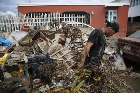 Toa Baja, Puerto Rico -- 9/30/2017 - Kened Joel Torres, 18, pulls debris out of his home and onto a growing pile on the street after Hurricane Maria. (Jessica Rinaldi/Globe Staff) Topic: Reporter: