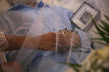 Corozal, Puerto Rico -- 10/02/2017 - Ana Ruiz reaches out to adjust the rosary beads on her husband's hand during his wake. (Jessica Rinaldi/Globe Staff) Topic: Reporter: