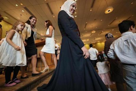 NOT FOR GETTY. Wellesley, MA., 09/30/17, Asmaa smiles as she and walks down from the bima at Temple Beth Elohim on Yom Kippur with the Jewish volunteers and the other Syrian families. Suzanne Kreiter/Globe staff