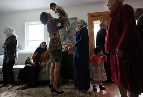 NOT FOR GETTY. Wellesley, MA., 09/30/17, The Syrian families and Jewish volunteers, gather at a party before walking down the street to Temple Beth Elohim on Yom Kippur. Volunteer Barbara Shapiro holds the youngest Syrian child. Suzanne Kreiter/Globe staff