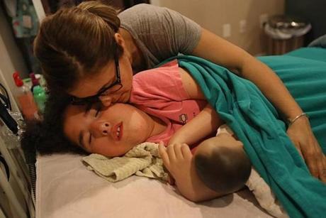 Dracut, Ma., 06/08/17, The night before the Jack Johnson concert, Noelia kisses Abi goodnight. Noelia Ferreira has gone over 100 days without skilled nursing care for her severely disabled 15 year old daughter Abi. Suzanne Kreiter/Globe Staff