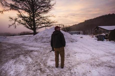 Norman Davenport looked out over his farm as the sun rises while taking a break from tending to his dairy cows.