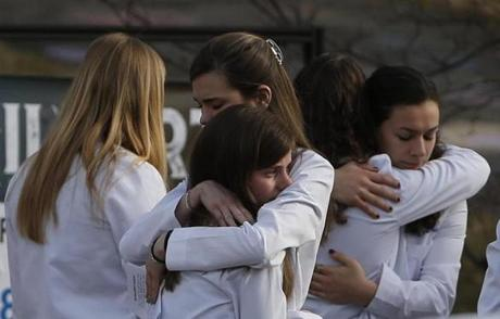 College of Osteopathic Medicine classmates embraced after the funeral for Deane Stryker.