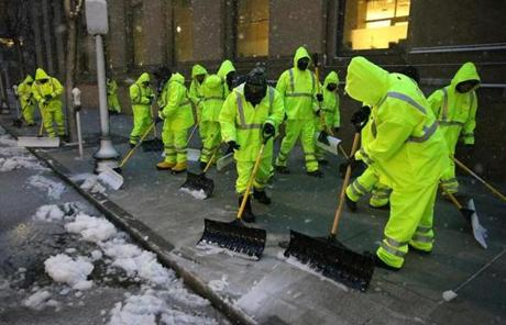 Workers cleared the sidewalk on Saint James Avenue in Boston.