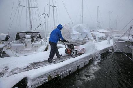 Brian Aufiero moved snow off the docks at the Constitution Marina in Charlestown.