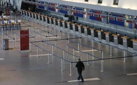 A man walked past an empty ticketing area for Delta at a deserted Logan Airport after a Nor'easter canceled the majority of flights.