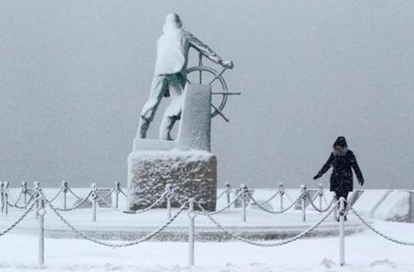 With the Fishermen's Memorial covered in snow, Linda Giovanni took her daily walk in blizzard conditions in Gloucester.