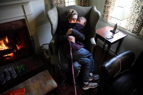 Nelson, NH- September 03, 2017: Roberta Biscan and her son, Connor Biscan, 13, embraced while resting by the fire during a family gathering in Nelson, N.H., last September. It had been a tough day. Connor is an affectionate, friendly boy who is exceptionally close to his relatives, especially his mother. But he is also a child who struggles to manage his powerful reactions to disappointments, often taking out his anger on his mother. (Craig F. Walker/Globe Staff) section: metro reporter: kowalczyk