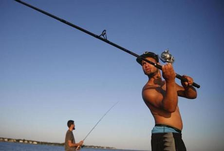East Lyme, CT -- 7/9/2017 - Josua Gonzalez (cq) of Springfield, (R) casts as he and Anthony Vega fish for striped bass at Rocky Neck State Park. (Jessica Rinaldi/Globe Staff) Topic: XXXXXXbestbeaches Reporter: