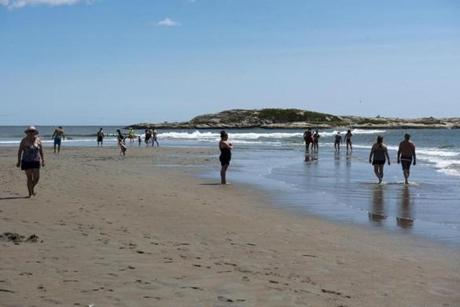 Phippsburg, ME - 8/6/17 - Beachgoers before a sandbar submerged under cresting waves at the Popham Beach State Park on Sunday, August 6, 2017. The beach is known for shell collecting at low-tide dramatic dune erosion. (Nicholas Pfosi for The Boston Globe) Topic: XXXXXXbestbeaches