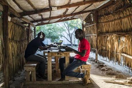 "Kakuma, Kenya - 5/8/2018 - Students Jimmy Onono(L) and Ajak Mayen go over course work on a laptops at the facility where Southern New Hampshire University has a degree program in the the UNHCR refugee camp in Kakuma, Kenya, May 8, 2018. The competency-based program, which has little traditional classroom time, provides what one student called an oasis from refugee life in the camp where they can not only have a work environment with stable internet access and electricity but also find camaraderie and support from schoolmates from multiple backgrounds. Established in 1992 following the arrival the ""Lost Boys of Sudan' and a population of nearly 190,000, the camp now resembles a sprawling shanty town with an infrastructure that includes, shops, restaurants, trades, and an underground power grid that in some ways surpasses the quality of life of the host town of Kakuma.. (Keith Bedford/Globe Staff)"