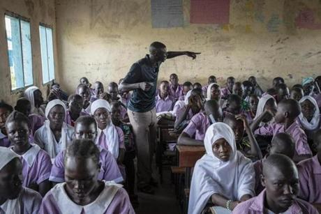 "Kakuma, Kenya - 5/11/2018 - Teacher Kuku Kurimagi Agoumi, a refugee from South Sudan and a student of SNHU's online degree program, leads his class in study at a school at the UNHCR refugee camp in Kakuma, Kenya, May 11, 2018. Teaching is one of the few jobs refugees are authorized to hold in the camp. Established in 1992 following the arrival the ""Lost Boys of Sudan' and a population of nearly 190,000, the camp now resembles a sprawling shanty town with an infrastructure that includes, shops, restaurants, trades, and an underground power grid that in some ways surpasses the quality of life of the host town of Kakuma. (Keith Bedford/Globe Staff)"