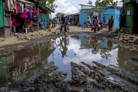 "Kakuma, Kenya - 5/18/2018 - People make their ways along a pool of standing water in the UNHCR refugee camp in Kakuma, Kenya, May 18, 2018. Even after minor rains water settles into pools that cause muddy and difficult to pass conditions on roads. Established in 1992 following the arrival the ""Lost Boys of Sudan' and a population of nearly 190,000, the camp now resembles a sprawling shanty town with an infrastructure that includes, shops, restaurants, trades, and an underground power grid that in some ways surpasses the quality of life of the host town of Kakuma.. (Keith Bedford/Globe Staff)"