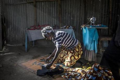 "Kakuma, Kenya - 5/8/2018 - Achayo Loum, a student of Southern New Hampshire University's online degree program for refugees, works on a dress at her shop in the UNHCR refugee camp in Kakuma, Kenya, May 8, 2018. Loum, a mother of four girls and a refugee from South Sudan, fled the violence in her country in 2001 and found a safe haven in Kenya as a teen-ager. She began the program as a way to seek new opportunities and a possible way out of living in a refugee camp for herself and her children. The competency-based program, which has little traditional classroom time, provides what one student called an oasis from refugee life in the camp where they can not only have a work environment with stable internet access and electricity but also find camaraderie and support from schoolmates from multiple backgrounds. Established in 1992 following the arrival the ""Lost Boys of Sudan' and a population of nearly 190,000, the camp now resembles a sprawling shanty town with an infrastructure that includes, shops, restaurants, trades, and an underground power grid that in some ways surpasses the quality of life of the host town of Kakuma.. (Keith Bedford/Globe Staff)"