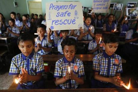 FILE - In this July 9, 2018, file photo, students at a school in Ahmadabad, India, hold candles and pray for a group of Thai youth soccer players and their coach who have been trapped since June 23, in Mae Sai, Chiang Rai province, northern Thailand. For the boys and their coach, we have only a hint of what it might have been like. But for the rest of us, watching from afar as the world's journalists beamed us live shots and the unknowable became known drip by captivating drip, we knew only one thing: It was hard to look away. (AP Photo/Ajit Solanki, File)