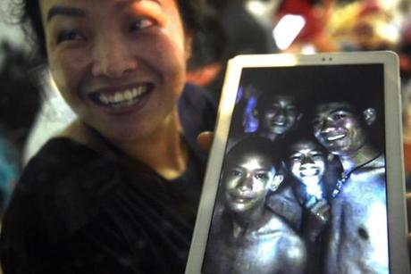 "CORRECTION - Thanaporn Promthep, mother of one of the 12 missing boys, displays an image believed to have been taken in 2017 of her son Duangpetch Promthep, nicknamed ""Dom"" (pictured 2nd R-with light) and his football coach Ekkapol Chantawong (R), after hearing the news the group was found, near the Tham Luang cave at the Khun Nam Nang Non Forest Park in the Mae Sai district on July 2, 2018. Twelve boys and their football coach trapped in a flooded Thai cave for nine days were ""found safe"" on late July 2, in a miracle rescue after days of painstaking searching by divers. The two boys at L are not trapped in the cave. / AFP PHOTO / LILLIAN SUWANRUMPHA / The erroneous mention[s] appearing in the metadata of this photo by LILLIAN SUWANRUMPHA has been modified in AFP systems in the following manner: [clarifying information, as well as adding names]. Please immediately remove the erroneous mention[s] from all your online services and delete it (them) from your servers. If you have been authorized by AFP to distribute it (them) to third parties, please ensure that the same actions are carried out by them. Failure to promptly comply with these instructions will entail liability on your part for any continued or post notification usage. Therefore we thank you very much for all your attention and prompt action. We are sorry for the inconvenience this notification may cause and remain at your disposal for any further information you may require.LILLIAN SUWANRUMPHA/AFP/Getty Images"