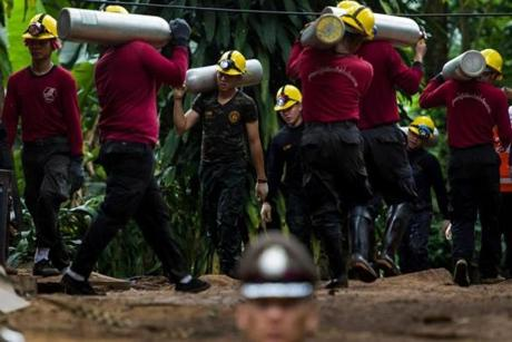 Thai soldiers carry oxygen tanks as rescue operations continue for the 12 boys and their football team coach trapped in Tham Luang cave at Khun Nam Nang Non Forest Park in the Mae Sai district of Chiang Rai province on July 7, 2018. More than 100 chimneys are being drilled into the mountainside in a frantic bid to reach a Thai youth football team trapped in a cave complex below, the head of the rescue mission said on July 7. / AFP PHOTO / YE AUNG THUYE AUNG THU/AFP/Getty Images