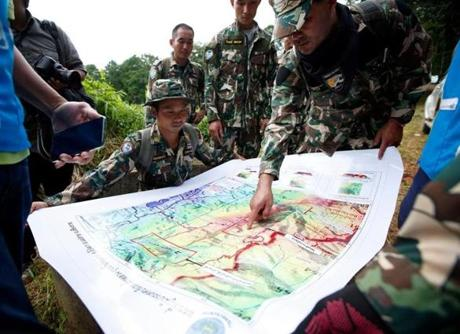 Mandatory Credit: Photo by RUNGROJ YONGRIT/EPA-EFE/REX/Shutterstock (9744618a) Thai forest rangers examine a map as they view a possible drilling option during the ongoing rescue operations for the child soccer team and their assistant coach, at a mountain forest near Tham Luang cave in Khun Nam Nang Non Forest Park, Chiang Rai province, Thailand, 07 July 2018. Operations are underway to safely bring out the 13 members of youth soccer team including their assistant coach who have been trapped in Tham Luang cave since 23 June 2018. Rescue efforts continue for missing members of Thai youth soccer team found alive in cave, Chiang Rai, Thailand - 07 Jul 2018