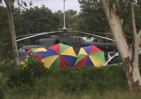 Local police place umbrellas around an evacuation helicopter as the remaining trapped boys and their coach are extracted from a cave in Mae Sai, Chiang Rai province, northern Thailand on Tuesday, July 10, 2018. (AP Photo/Sakchai Lalit)
