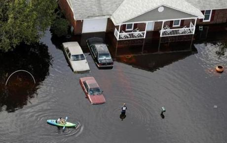 A man paddled a kayak through a flooded neighborhood in Fayetteville N.C. Monday