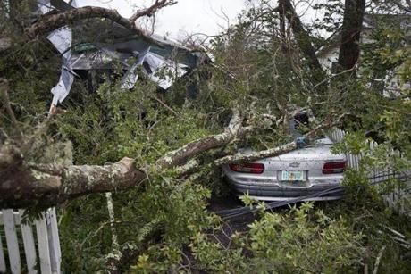 A tree lay on a home and car after hurricane Michael passed through the area.