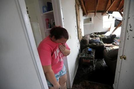Kaylee O'Brian wept inside her home after several trees fell on it.