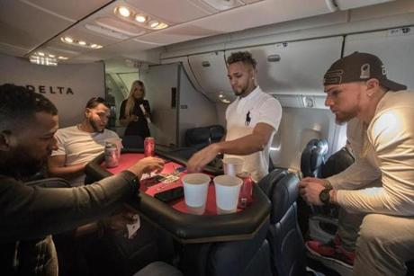 Somewhere between Los Angeles and Boston-- October 29, 2018-Stan Grossfeld/ Globe Staff---The Red Sox charter on the way back from winning the World Series in Los Angeles. Eduardo Nunez had an ace under the table as he played 21 with Eduardo Rodriquez, Xander Bogaerts and Christian Vazquez.