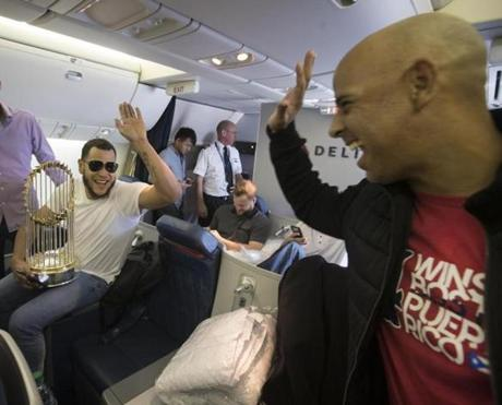Somewhere between Los Angeles and Boston-- October 29, 2018-Stan Grossfeld/ Globe Staff—Sox pitcher Eduardo Rodriquez get high-fived by Sox manager Alex Cora on the Red Sox charter from Los Angeles.