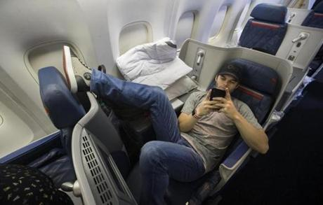 Somewhere between Los Angeles and Boston-- October 29, 2018-Stan Grossfeld/ Globe Staff---The Red Sox charter on the way back from winning the World Series in Los Angeles. Sox outfielder Andrew Benintendi checked his phone.