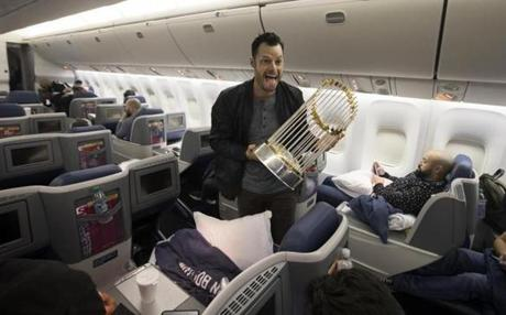 Somewhere between Los Angeles and Boston-- October 29, 2018-Stan Grossfeld/ Globe Staff---The Red Sox charter on the way back from winning the World Series in Los Angeles. Sox reliever Joe Kelly with the trophy.
