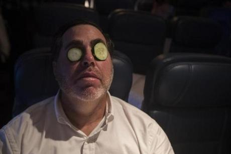 Somewhere between Los Angeles and Boston-- October 29, 2018-Stan Grossfeld/ Globe Staff---The Red Sox charter on the way back from winning the World Series in Los Angeles. Bullpen coach Craig Bjornson used cucumber slices to rest his weary eyes.