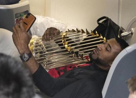Somewhere between Los Angeles and Boston-- October 29, 2018-Stan Grossfeld/ Globe Staff---The Red Sox charter on the way back from winning the World Series in Los Angeles. Third baseman Eduardo Nunez took a selfie with the trophy.